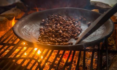 Schließen Sie oben von der Kakaobohne innerhalb eines metallischen Behälters, über einem hölzernen Ofen und Röstkakaobohnen Standard-Bild