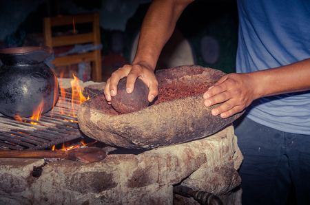 People grinding a cacao beans over a rock, next to a wood stove