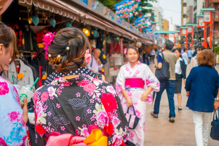 TOKYO, JAPAN JUNE 28 - 2017: Unidentified woman taking a picture of her friend in the Buddhist Temple Sensoji in Tokyo, Japan. The Sensoji temple in Asakusa area is the oldest temple in Tokyo