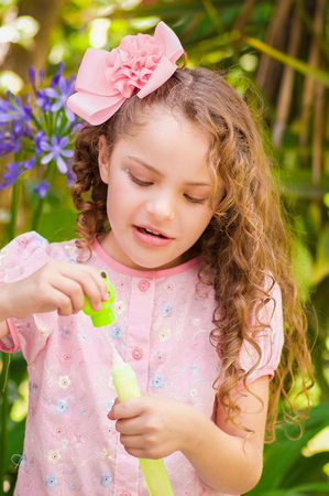 Happy little curly girl playing with soap bubbles on a summer nature, wearing a pink dress and flower in her head, in a blurred nature background