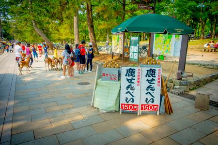 cervus: Nara, Japan - July 26, 2017: Informative sign with food for the wild deer in Nara, Japan. Nara is a major tourism destination in Japan