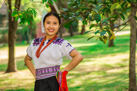 clothe: Young indigenous woman wearing a typical andean clothes, holding in her hand a colorful blanket