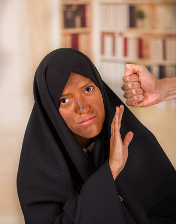Portrait of a muslim girl wearing a hijab, puting her hand to protect herslef from a fist of a white man, in a blurred background