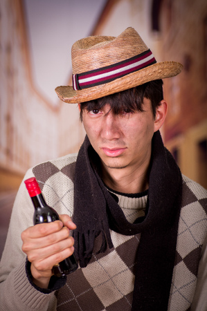 Close up of a sad homeless young man in the streets, wearing a hat and a scarf, and holding a bottle of wine in his hand, in a blurred background Stock Photo