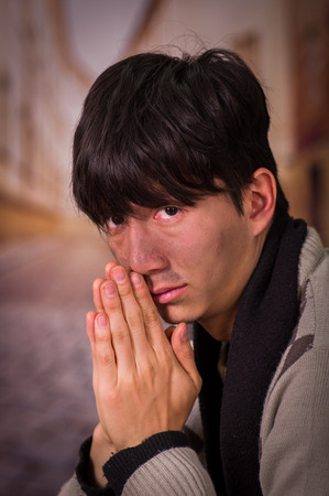 Portrait of a homeless young man in the streets, praying for food in a blurred background Stock Photo