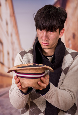Close up of a sad homeless young man in the streets, with a hat in his hands, asking for money, in a blurred background