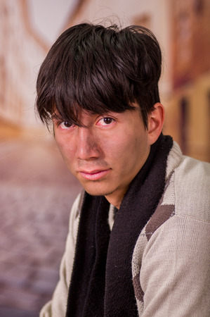 Portrait of a homeless young man in the streets, in a blurred background Stock Photo