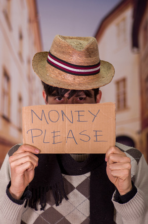 Close up of a homeless with cardboard description of money please, wearing a hat, in a blurred background