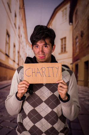 Close up of a homeless with cardboard description of charity, in a blurred background Stock Photo