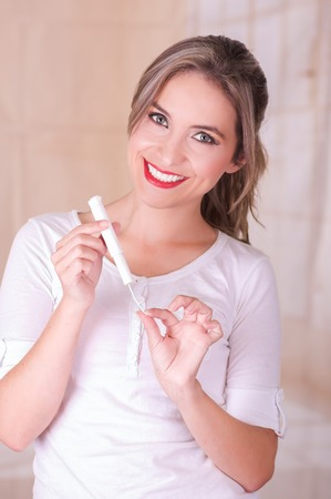 Young beautiful smiling woman holding a menstruation cotton tampon in her hand