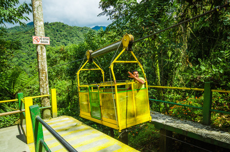 MINDO, ECUADOR - AUGUST 27, 2017: Unidentified man inside of the Tarabita crossing deep valley, up to 152 m above the ground located in Mindo, Ecuador