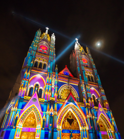 QUITO, ECUADOR - AUGUST 9, 2017: Beautiful view at night of the neo - gothic style Basilica of the National Vow illuminated with colorful lights during the Quito light festival, with a full moon in the sky