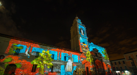 Quito, Pichincha Ecuador - August 9 2017: Close up of spectacle of lights projected on the facade of Church of Santo Domingo, with some yellow iguana, rocks and sea representing biodiversity, during the Quito light festival