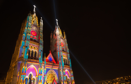 QUITO, ECUADOR - AUGUST 9, 2017: Beautiful view at night of the neo - gothic style Basilica of the National Vow illuminated with colorful lights during the Quito light festival
