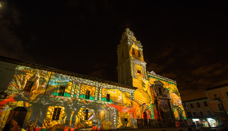 Quito, Pichincha Ecuador - August 9 2017: Close up of spectacle of lights projected on the facade of Church of Santo Domingo, with some yellow iguana representing biodiversity, during the Quito light festival