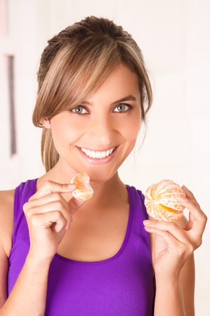 Beautiful young smiling woman wearing a purple-shirt and eating a tangerine in a white background