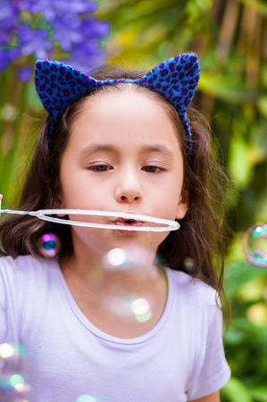 Happy little girl playing with soap bubbles on a summer nature, wearing a blue ears tiger accessories over her head in a blurred nature background