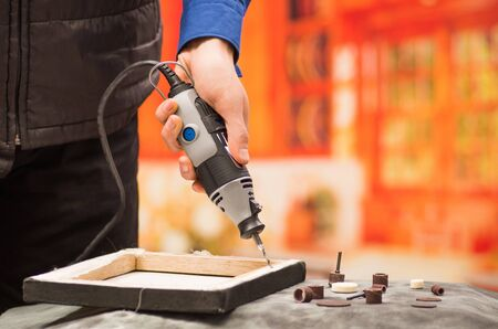 Closeup of a hardworker man drilling a wooden frame with his drill, with drilling accessories over a gray table in a blurred background