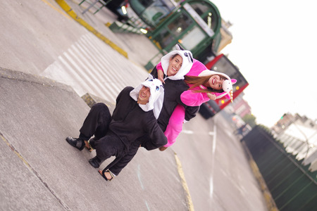 Close up of a happy group of friends, playing in the streets and wearing different costumes, one woman wearing a pink unicorn costume, other woman a panda costume and the man wearing a cat costume, in the city of Quito