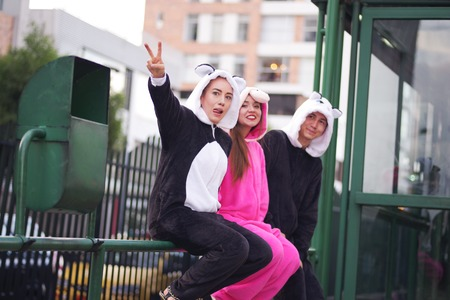 Close up of a happy group of friends, waiting the public transportation and wearing different costumes, one woman wearing a pink unicorn costume, other woman a panda costume and the man wearing a cat costume, in the city of Quito Stock Photo