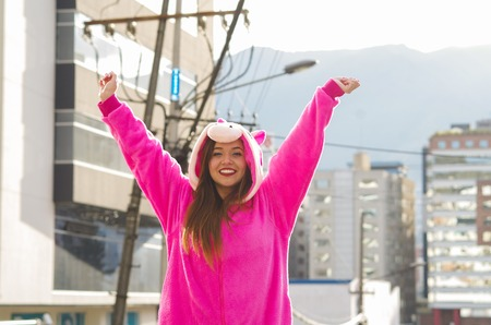 Close up of a beautiful smiling young woman wearing a pink unicorn costume, with both hands up at outdoors in the city of Quito Stock Photo