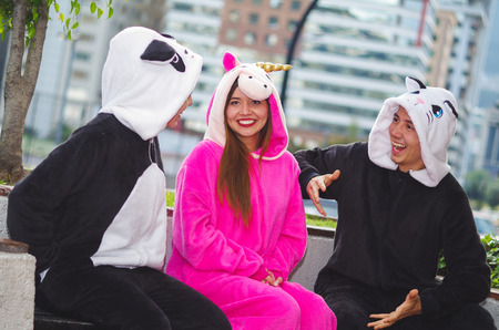 Close up of a happy group of friends having a fun conversation and wearing different costumes, one woman wearing a pink unicorn costume, other woman a panda costume and the man wearing a cat costume, in the city of Quito Stock Photo