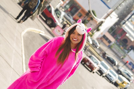 Portrait of a beautiful smiling young woman wearing an unicorn costume, at outdoors in the city of Quito Stock Photo