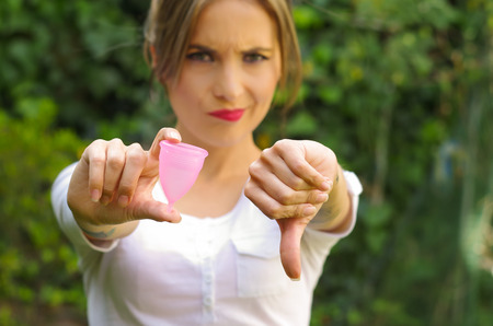 Close up of a young woman pointing in front of her a menstrual cup in one hand, Gynecology concept, ith her thums down rejecting the use of the mentrual cup, in a blurred background Stock Photo