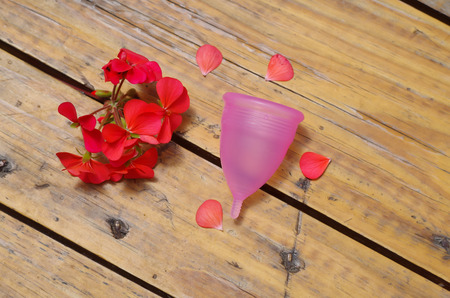 miserly: Feminine hygiene product - Menstrual cup next to a beautiful red flowers, in a wooden background Stock Photo