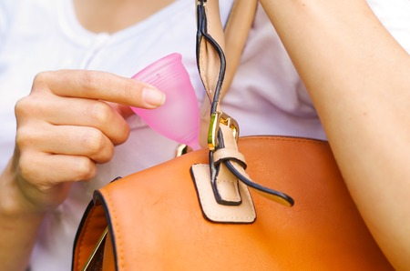 Close up of a young smiling beautiful woman keeping a menstrual cup inside of a purse. Gynecology concept Stock Photo