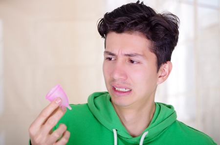 Close up of a man doing an disgusting face while is holding a menstrual cup in his hands, in a blurred background Imagens - 85269924