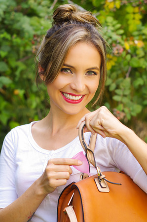 Close up of a young smiling beautiful woman keeping a menstrual cup inside of a purse. Gynecology concept, in a blurred background Stock Photo