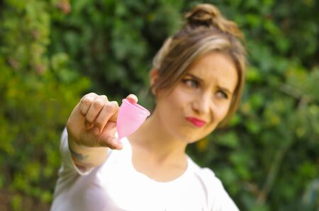 Close up of a young woman pointing in front of her a menstrual cup in one hand, Gynecology concept, in a blurred background