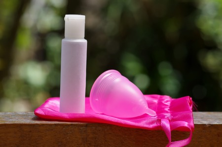 Close up of menstrual cup with cotton bag with a white flask of cream, in a blurred background