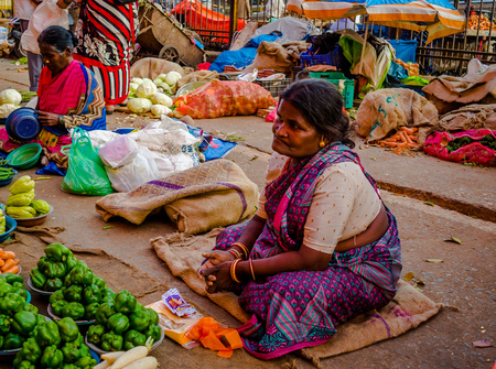 JAIPUR, INDIA - AUGUST 25 2017: Indian women sells assorted food in the streets in Jaipur, India. In India poor women often sell vegetables to earn a small cash income Editorial