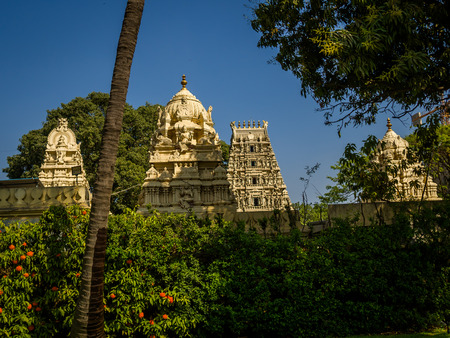 Beautiful view of a hindu temple with some sculptures around the building in a beautiful blue sky Stock Photo