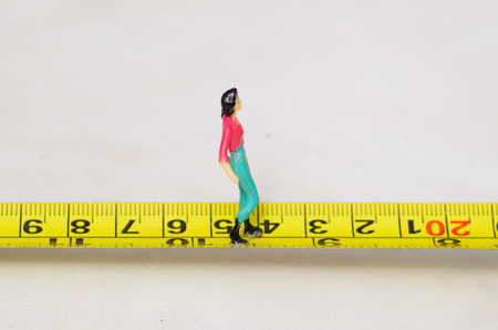 Miniature little people woman walking over a yellow tape measure isolated Stock Photo