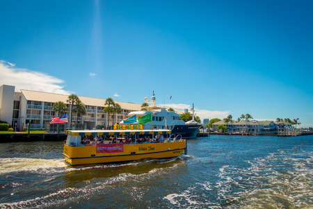 FORT LAUDERDALE, USA - JULY 11, 2017: Colorful yellow water taxi and a white yatch together sailing, with a gorgeous view of river walk promenade with buildings behind, in Fort Lauderdale, Florida Editorial