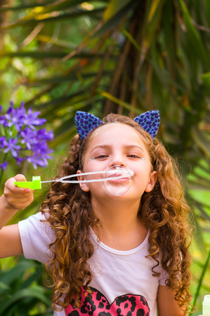 Happy little curly smiling girl playing with soap bubbles on a summer nature, wearing a blue ears of tiger accessories over her head in a blurred nature background