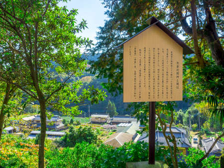 Informative sign of japanesse letter with a beautiful landscape of the mountain with some houses, in a gorgeous blue sky