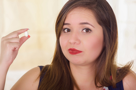 Portrait of a young woman holding in her hand a soft gelatin vaginal tablet or suppository, treatment of diseases of the reproductive organs of women and prevention of womens health Stock Photo