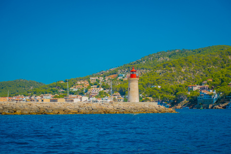 Beautiful view of Mallorca balearic islands, with a lighthouse and some buildings in the mountain in the horizon, with gorgeous blue water and a beautiful blue sky, in Spain
