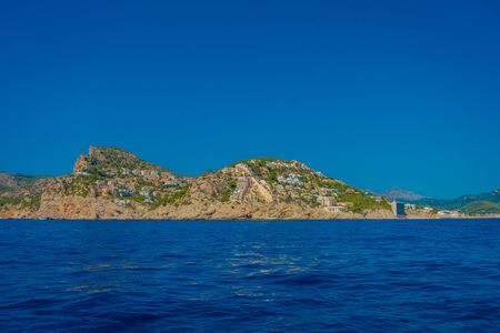 Beautiful view of Mallorca balearic islands, with some buildings in the mountain in the horizon, with gorgeous blue water and a beautiful blue sky, in Spain