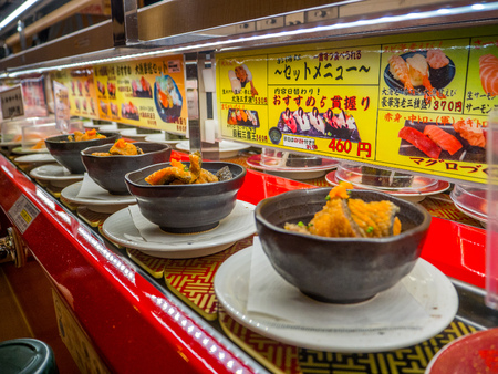 TOKYO, JAPAN -28 JUN 2017: Close up of assorted japanesse food over a table, inside of a kaitenzushi conveyor belt sushi restaurant in Tokyo Editorial