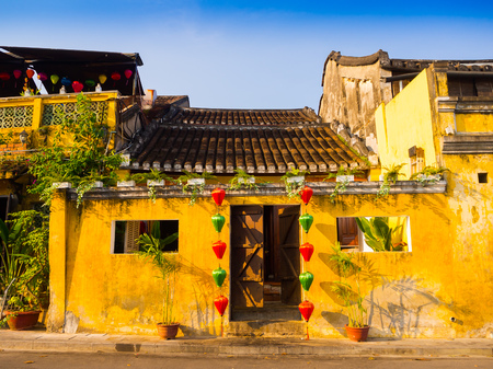 Green and red lanterns hanging outside of an old yellow house in Hoi An ancient town, UNESCO world heritage. Hoi An is one of the most popular destinations in Vietnam