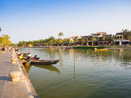 HOIAN, VIETNAM, SEPTEMBER, 04 2017: Traditional boats in front of ancient architecture in Hoi An, Vietnam. Hoi An is the Worlds Cultural heritage site, famous for mixed cultures architecture