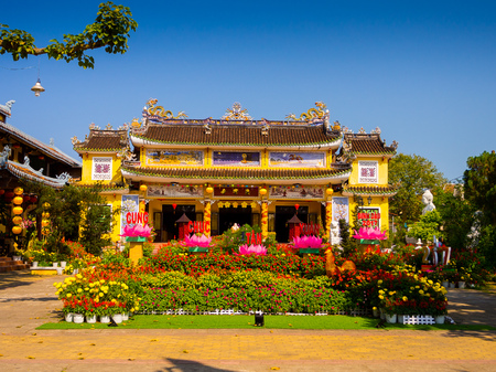 HOIAN, VIETNAM, SEPTEMBER, 04 2017: View of an ancient temple with a beautiful jarden with colorful flowers at hoian, in a sunny day in Vietnam Editorial