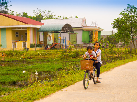 Hoian, Vietnam - August 05, 2017: Unidentified children biking in a road, back to home in Hoi An ancient town. Hoi An is one of the most popular destinations in Vietnam