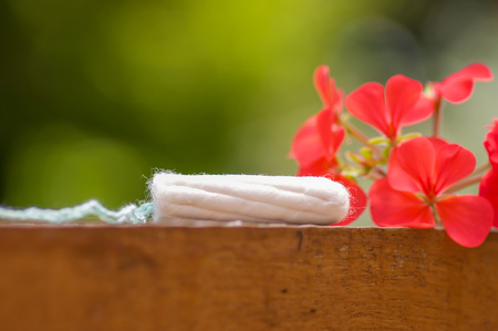 Feminine hygiene product - menstruation cotton tampon over a wooden structure with a beautiful red flower, in a blurred background Stock Photo