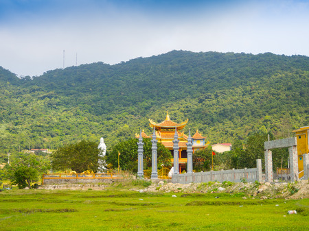 HOIAN, VIETNAM, SEPTEMBER, 04 2017: Beautiful view of an ancient temple in the horizont, with some green grass in the front, at hoian town in a sunny day in Vietnam Editorial